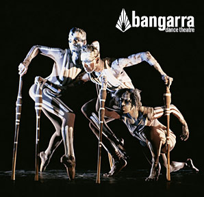 Bangarra Dance Theatre members painted up and holding on to sticks for balance.