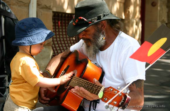 An Aboriginal man squatting on the footpath to let a toddler touch his guitar.