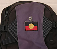A day pack with an Aboriginal flag stitched onto it.