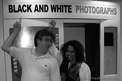 A white man and a black woman in front of a Black and white photography booth