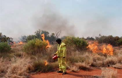 An Aboriginal man lighting fires in dry bushland.